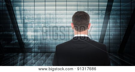Businessman looking in front of him in suit against room with large window looking on city