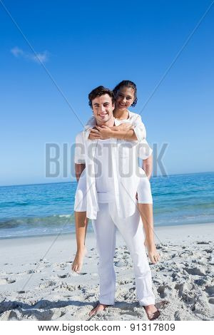 Handsome man giving piggy back to his girlfriend at the beach