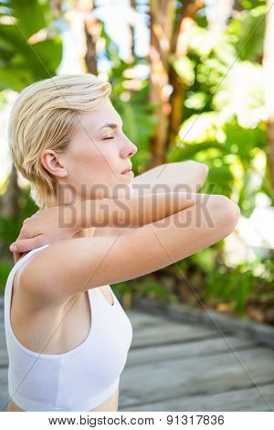 Fit blonde woman meditating outside on a sunny day
