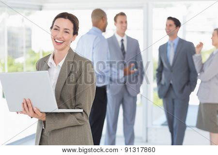 Businesswoman with his laptop and her colleagues behind in the office