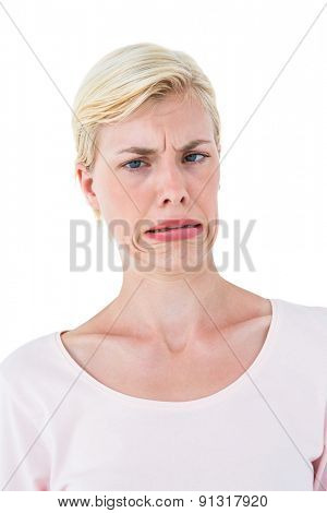 Blonde woman grimacing on white background