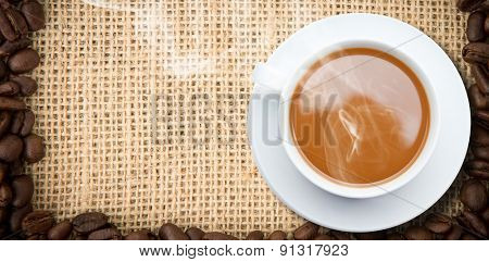 White cup of tea against frame of coffee beans