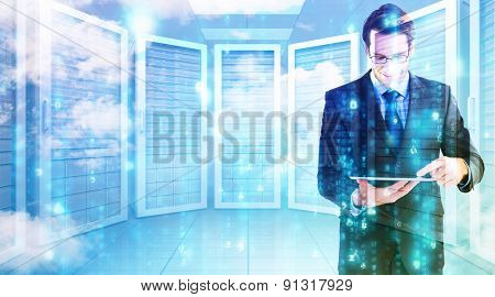 Businessman standing while using a tablet pc against server room