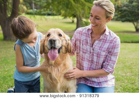 Mother and her daughter with their dog in the park on a sunny day