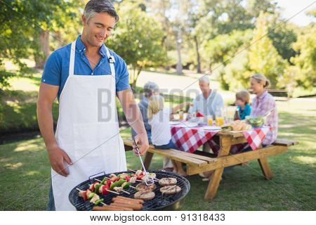 Happy man doing barbecue for his family in a sunny day