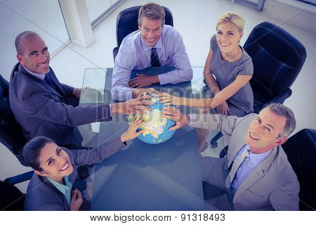 Business team putting hands on globe at a meeting