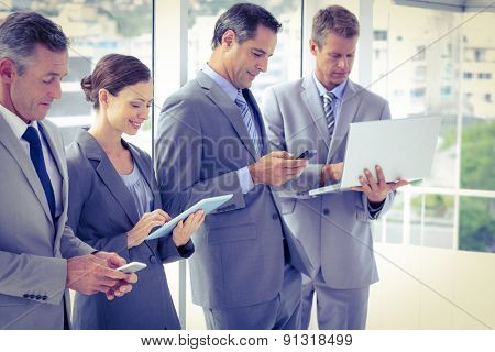 Business team using their media devices in the office