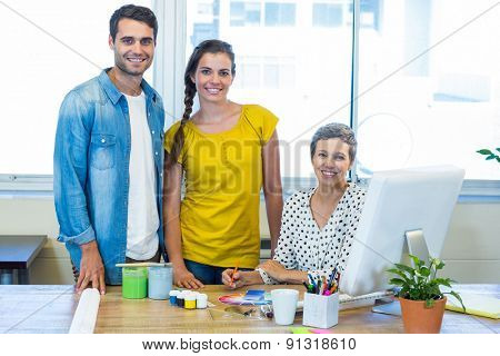 Casual business team smiling at camera during meeting in the office