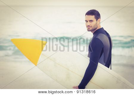 Man in wetsuit with a surfboard on a sunny day at the beach