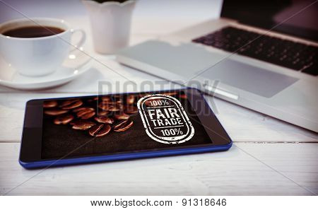 Fair Trade against desk with laptop and tablet