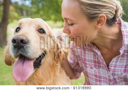 Happy blonde with her dog in the park on a sunny day