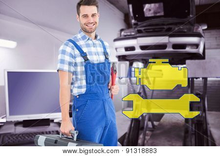 Smiling young male repairman carrying toolbox against auto repair shop
