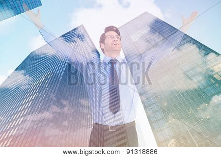 Cheering businessman with his arms raised up against skyscraper