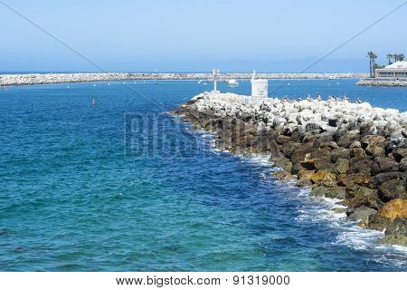 A view of King Harbor breakwater during a bright, sunny day reveals the shallow, turquoise water surrounding the bay.