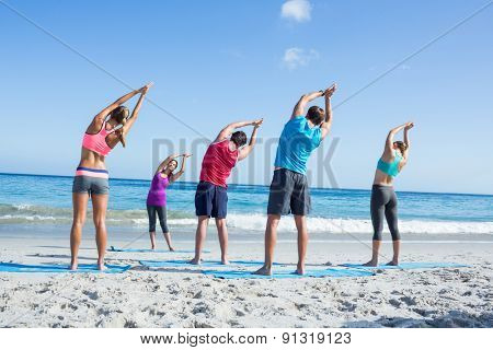 Friends stretching together with their teacher at the beach