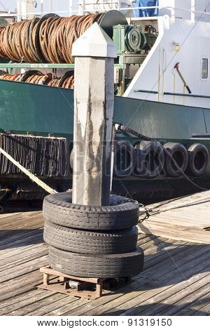 A dock pylon with used tires around it are used as means to tie up barges as they rest in their slips