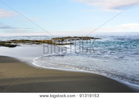 A beautiful pastel morning along a beach in Laguna California with gentle surf and a shoreline reef. B