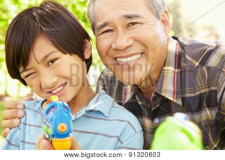 Boy and grandfather with water pistols
