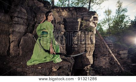 Elf Woman With The Magic Bow On The Rocks Background.