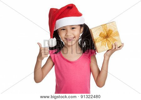 Little Asian Girl With Santa Hat And Gift Box  Thumbs Up