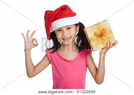 Little Asian Girl With Santa Hat And Gift Box Show Ok