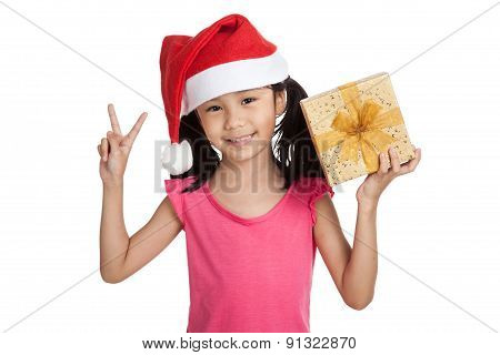 Little Asian Girl With Santa Hat And Gift Box Show 2 Fingers