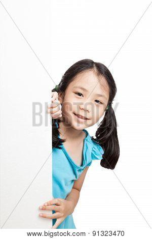 Little Asian Girl Peeking Behind A White Board