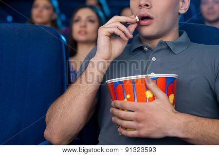 Man Eating Popcorn At The Cinema.
