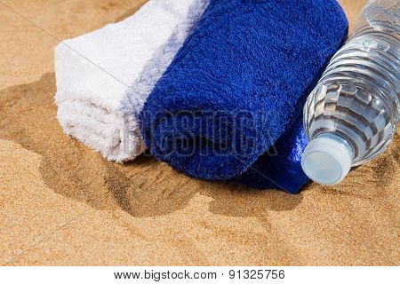 towels and bottle of water in sand