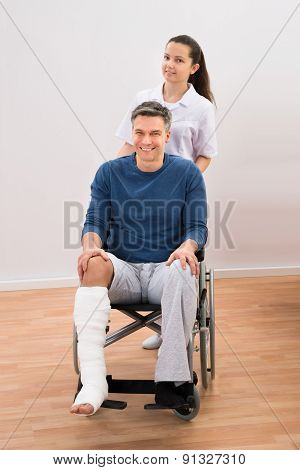 Doctor With Disabled Patient On Wheelchair