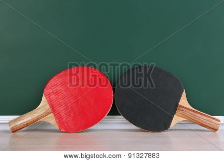 Table tennis rackets on blackboard background