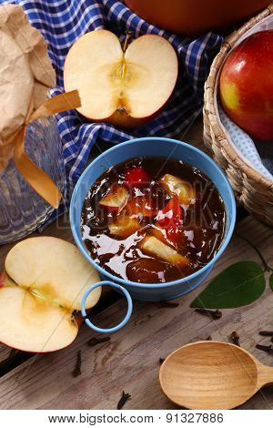 Apple jam in pail and fresh red apples on wooden table close-up