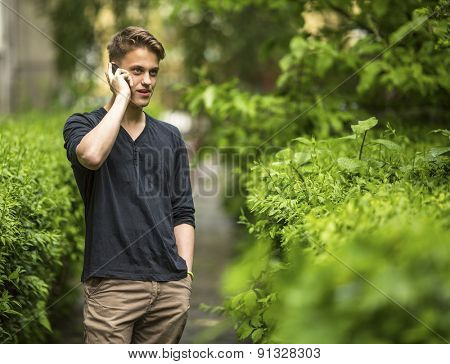 Young man talking on mobile phone outdoors.