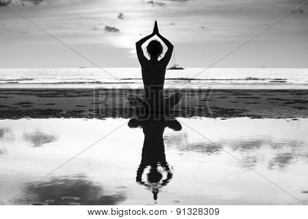 Silhouette of yoga woman on sea coast, contrasting black and white photo.