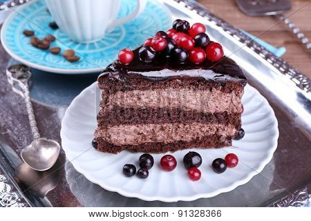 Delicious chocolate cake with berries on plate on table close up