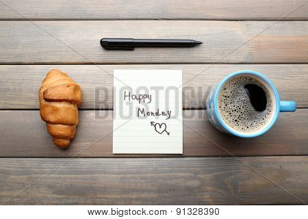 Cup of coffee with fresh croissant and Happy Monday massage on wooden background