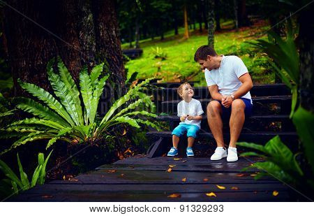 Happy Father And Son Sitting On Wooden Stairs In Rain Forest