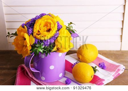 Composition with fresh spring flowers in water can on wooden background