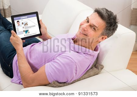 Man Chatting On Social Networking Website On Couch