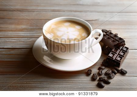 Cup of coffee latte art with grains and chocolate bar on wooden table background