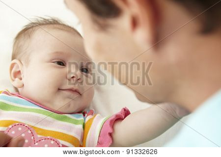 Father Playing With Baby Daughter At Home