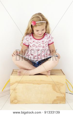 Young Girl Sitting On Wooden Toy Box Reading Book In Bedroom