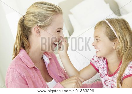 Mother And Daughter Playing Together In Bedroom