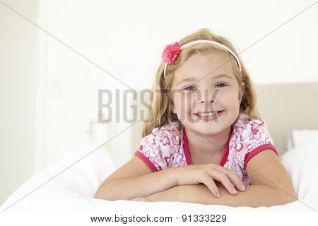 Young Girl Relaxing On Bed In Bedroom