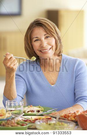 Senior Hispanic Woman Enjoying Meal At Home
