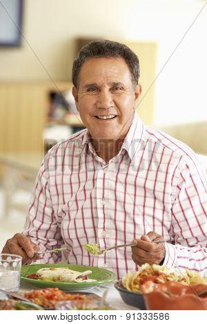 Senior Hispanic Man Enjoying Meal At Home