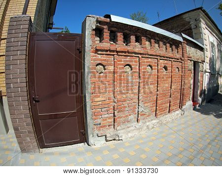Brick Wall With A Solid Iron Door On A City Street