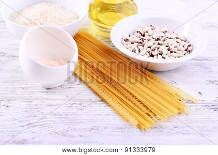 Pasta, beans, rice and olive oil on color wooden table background