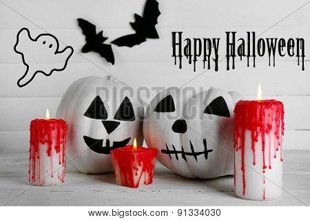 White Halloween pumpkins, candles on white wooden background