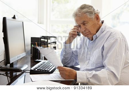 Senior Hispanic man working on computer at home